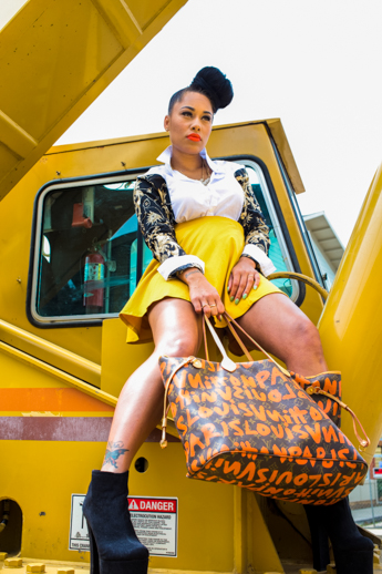 Photography of fashion savvy female model sitting on yellow machinery sporting a yellow skirt and handbag to match.
