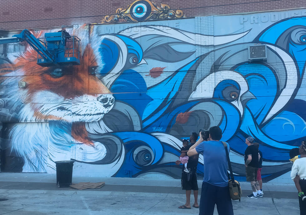 Photograph of Fel3000ft working on his latest mural as a crowd watches below